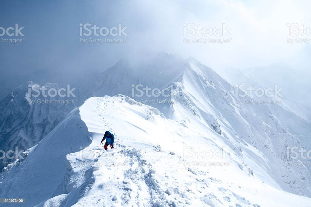 Ice Climber walks along mountain peak stock photo