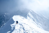 Ice Climber walks along mountain peak
