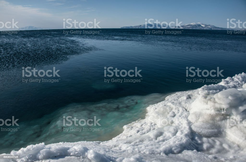 Ice coast and blue water of the Okhotsk Sea in winter stock photo