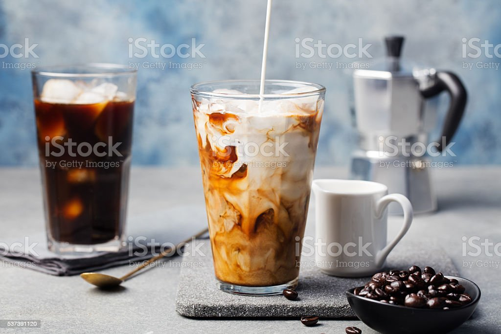 Ice coffee in a tall glass with cream poured over stock photo