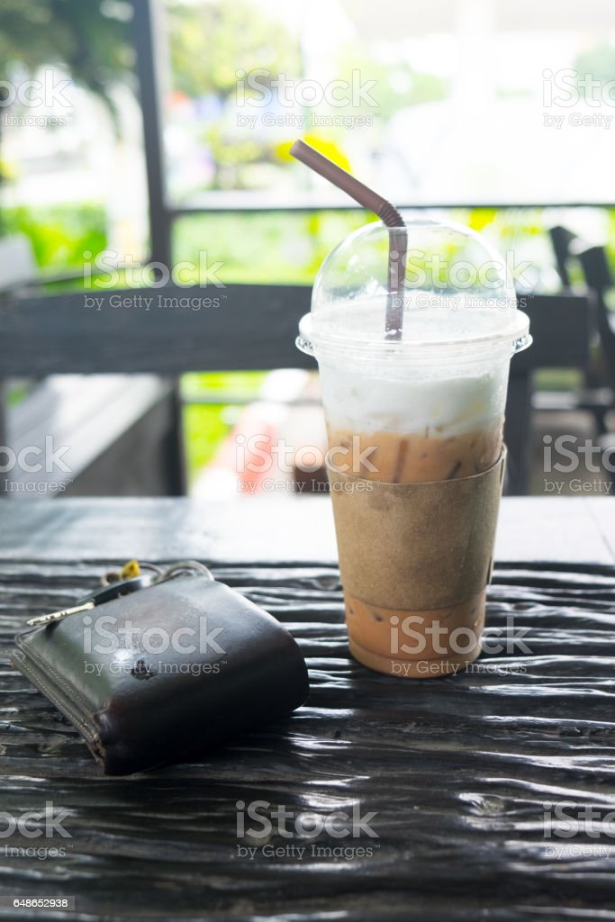 Ice coffee with wallet on wood table. stock photo