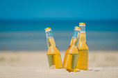 Ice cold beer bottles in the sand under the sun