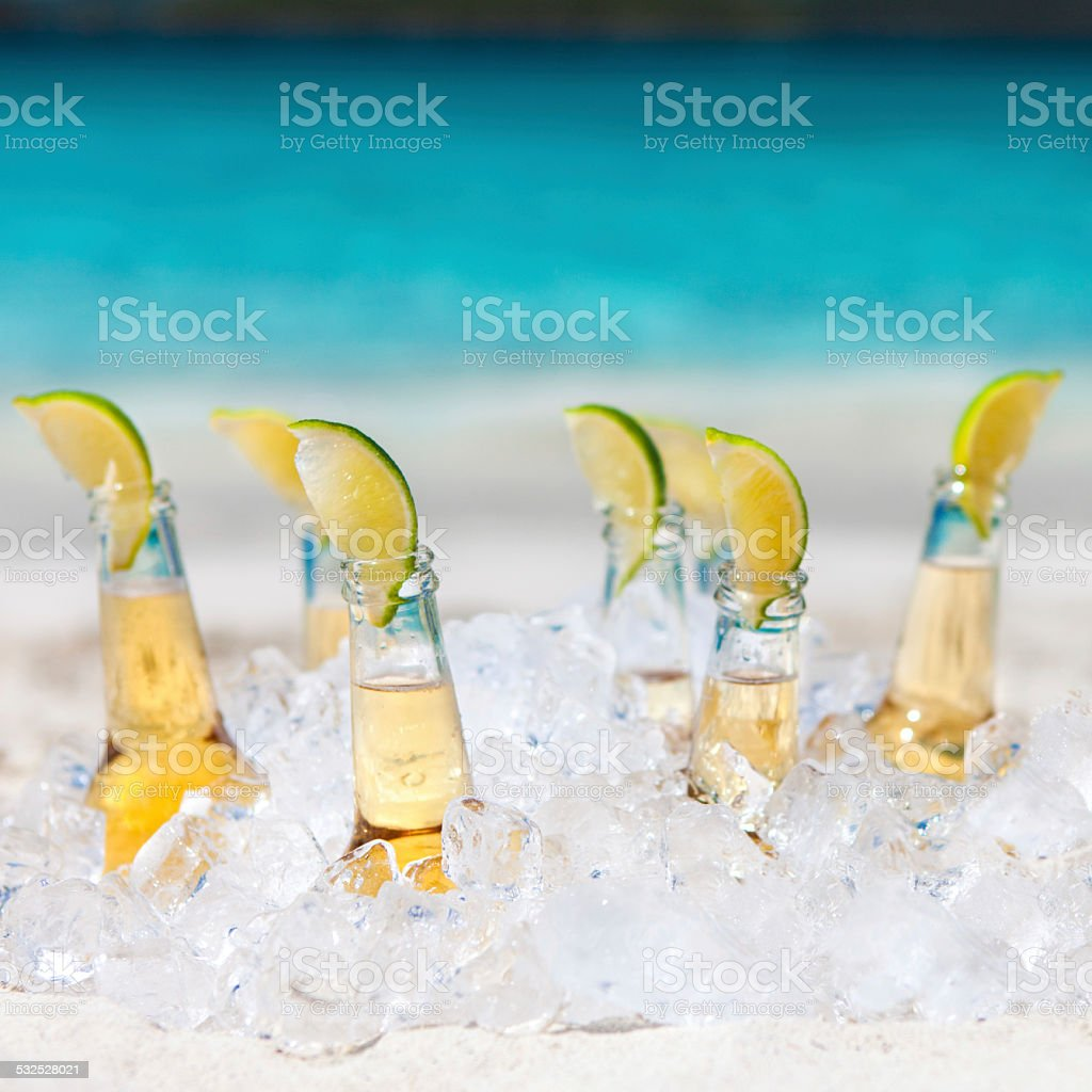 ice cold beers with limes on the Caribbean beach stock photo