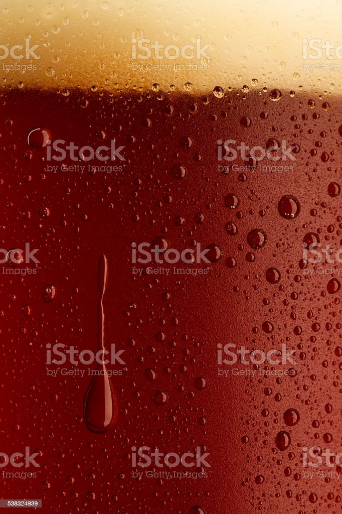 Ice cold  glass of dark beer  covered with water drops stock photo