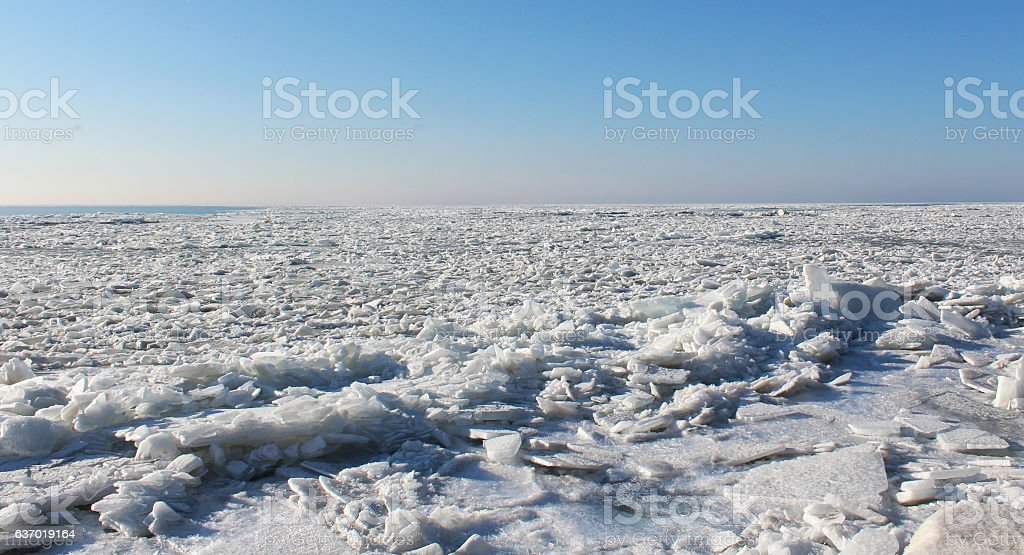 Ice cracks on frozen lake - winter stock photo