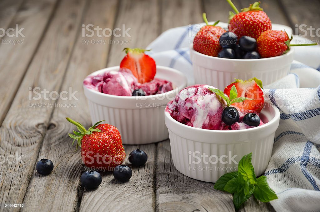 Ice cream with blueberries and strawberries in white bowl stock photo