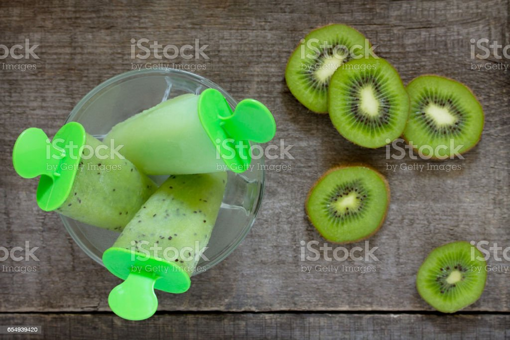 Ice cream with kiwi and fruit ice against a vintage wooden background, copy space. The concept of a healthy diet and detox diet. stock photo