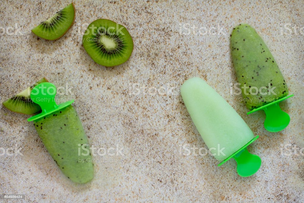 Ice cream with kiwi and fruit ice on a stone background, copy space. The concept of a healthy diet and detox diet. stock photo
