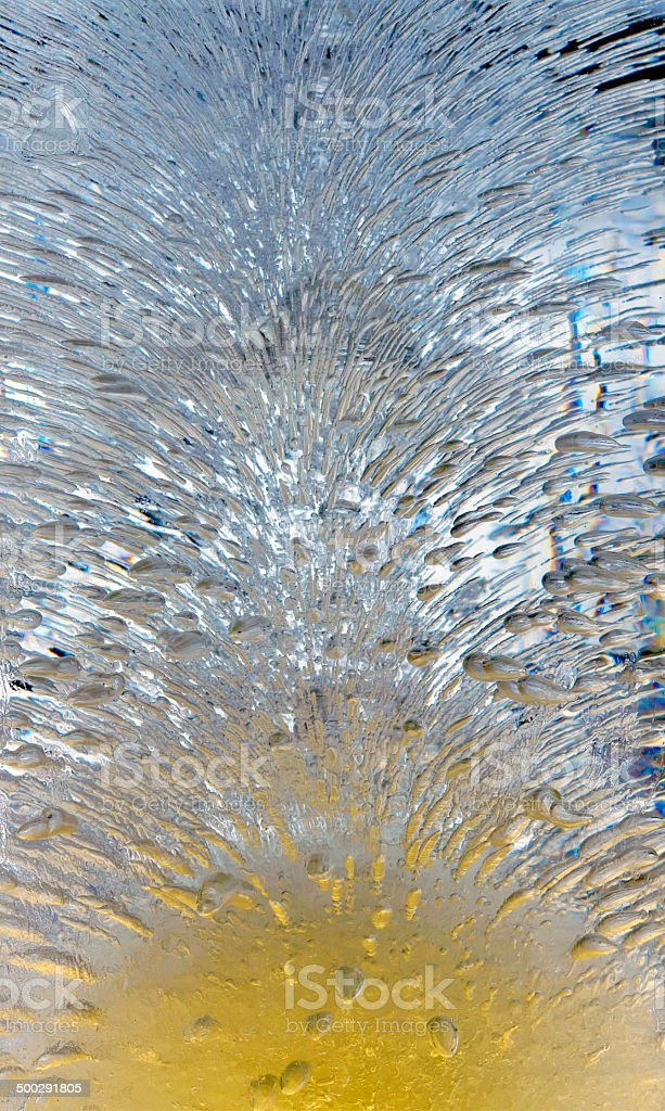 Ice crystal illuminated in yellow and blue royalty-free stock photo