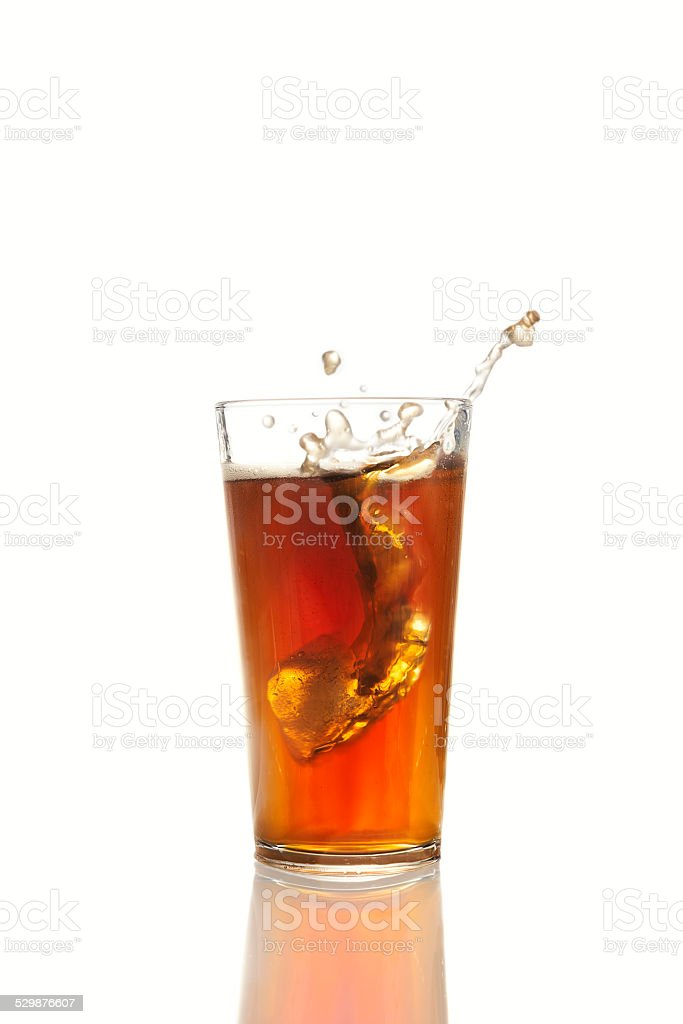Ice cube falling into glass of cola stock photo