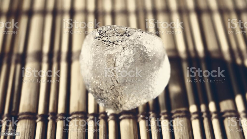 Ice cube on the wooden surface stock photo