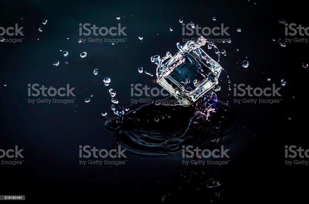 ice cube splashing into water, black background, stock photo
