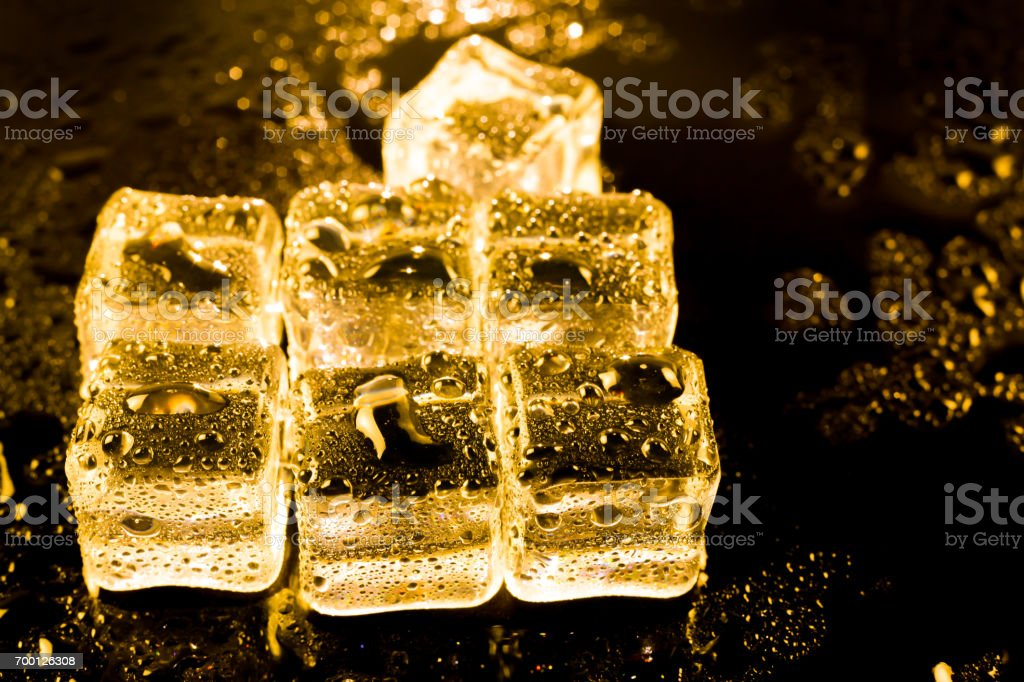 ice cubes and water drop on light golden background. stock photo