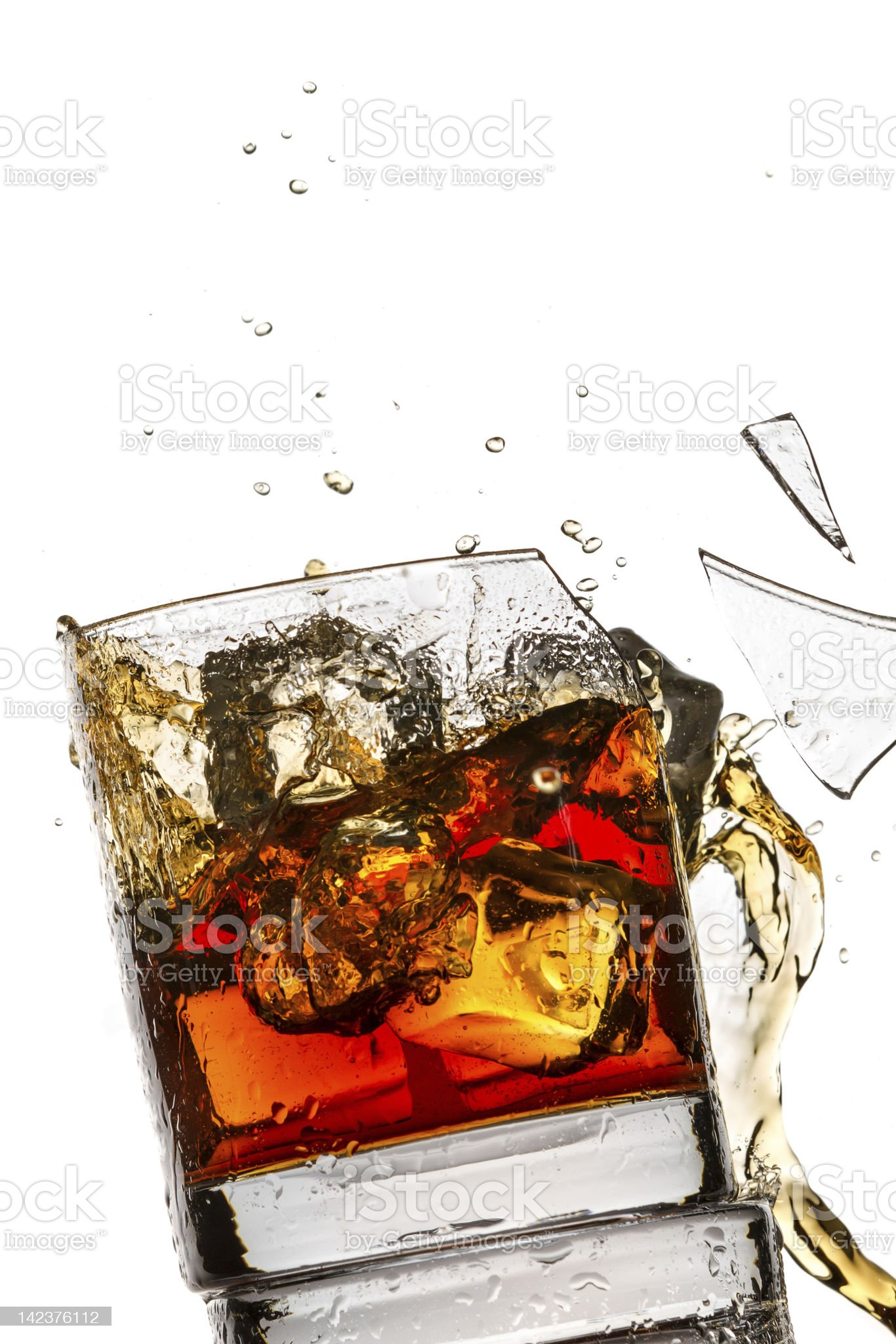 Ice cubes breaking whisky glass filled with bourbon royalty-free stock photo