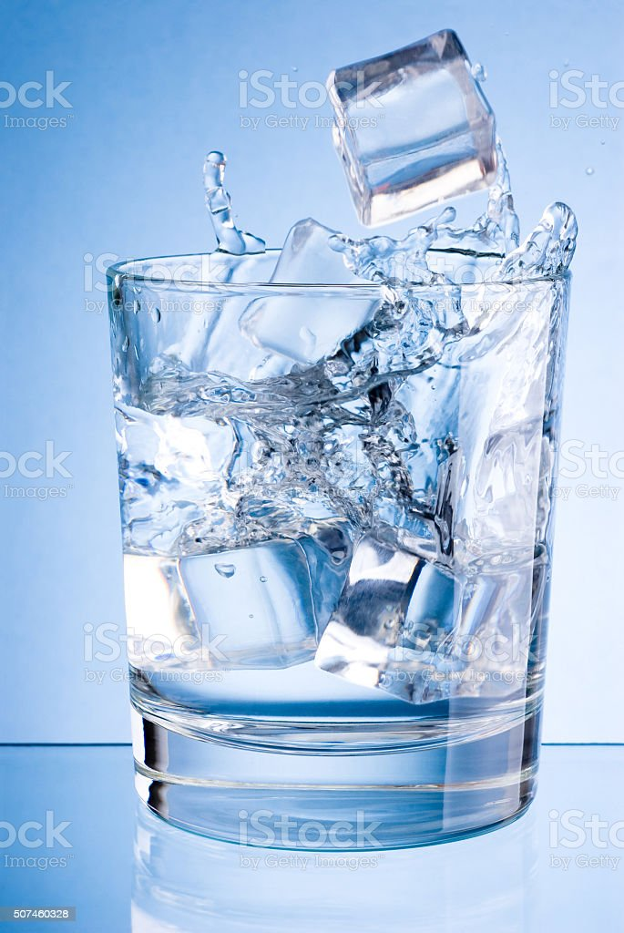 Ice cubes fall into glass of water on blue background stock photo