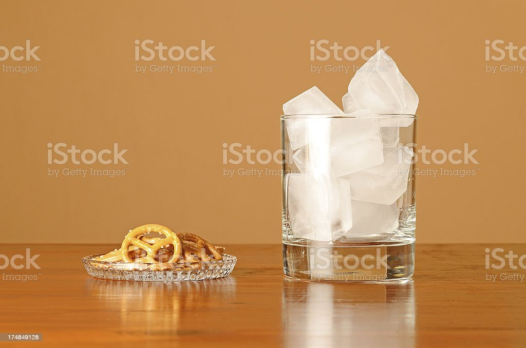 Ice cubes in empty glass with plate of pretzel royalty-free stock photo