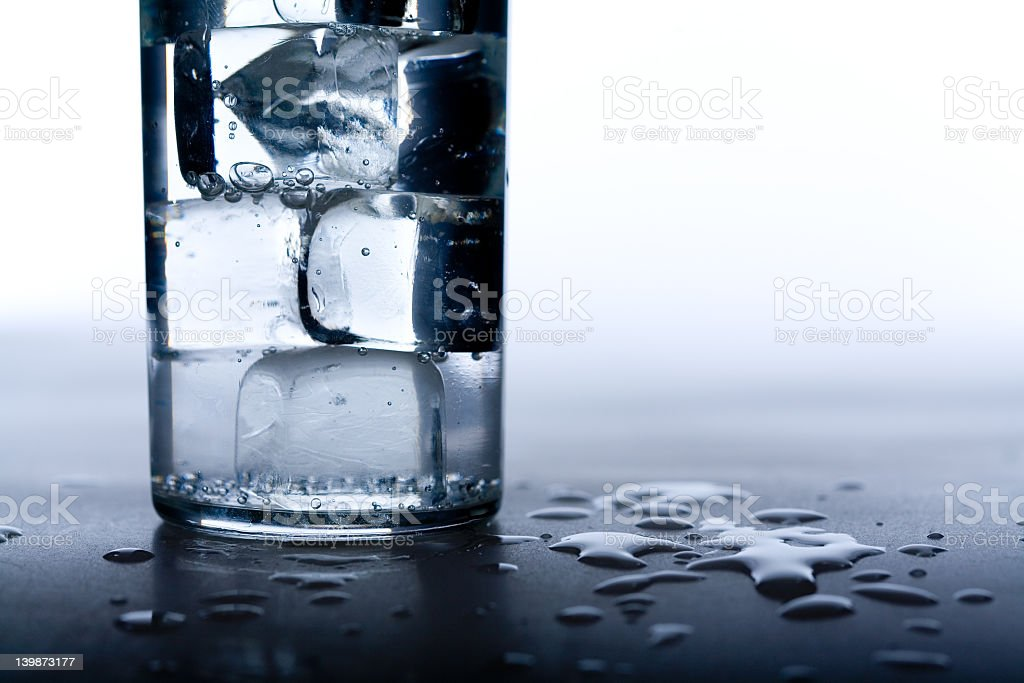 Ice cubes in water glass with water spilt on ground royalty-free stock photo