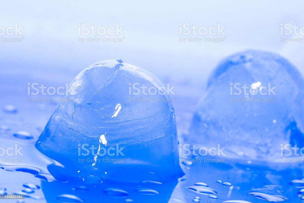 Cubos de gelo em um fundo azul foto de stock royalty-free
