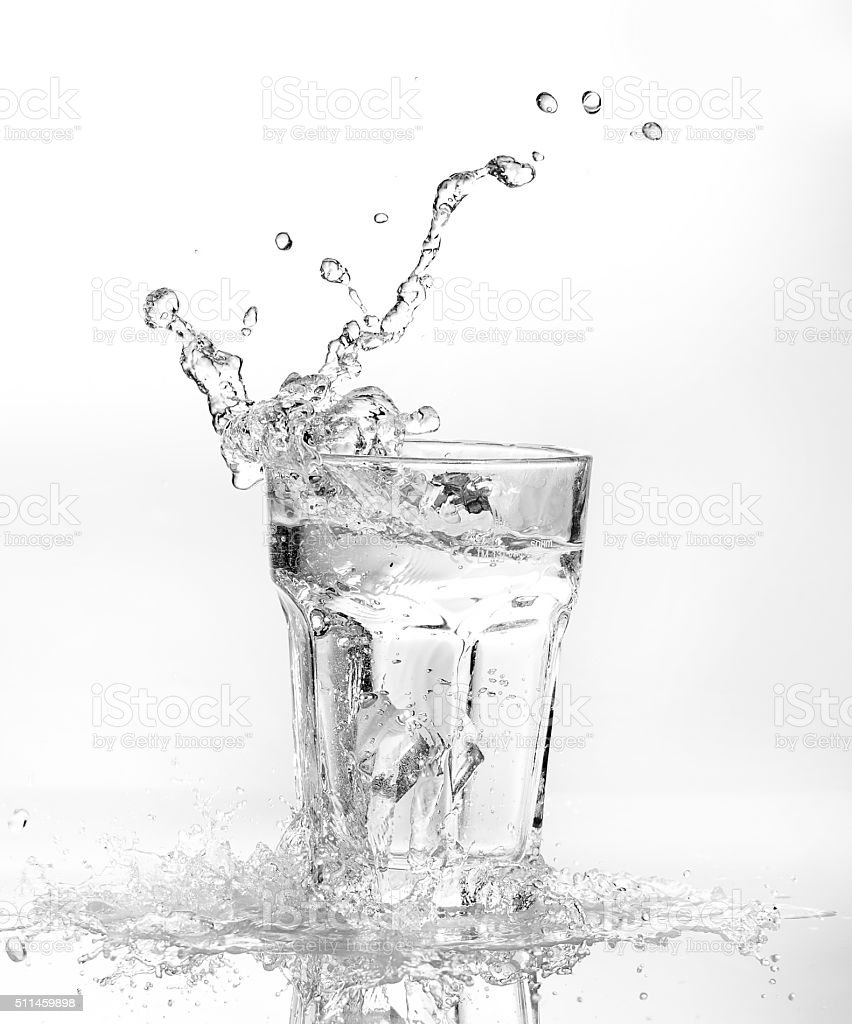 Ice cubes splashing into glass of water stock photo