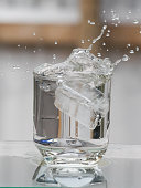 Ice cubes splashing into glass of water with Background blur
