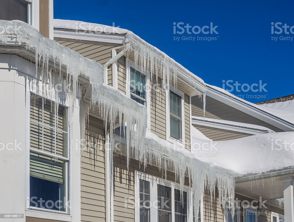 Ice dams and snow on roof and gutters stock photo