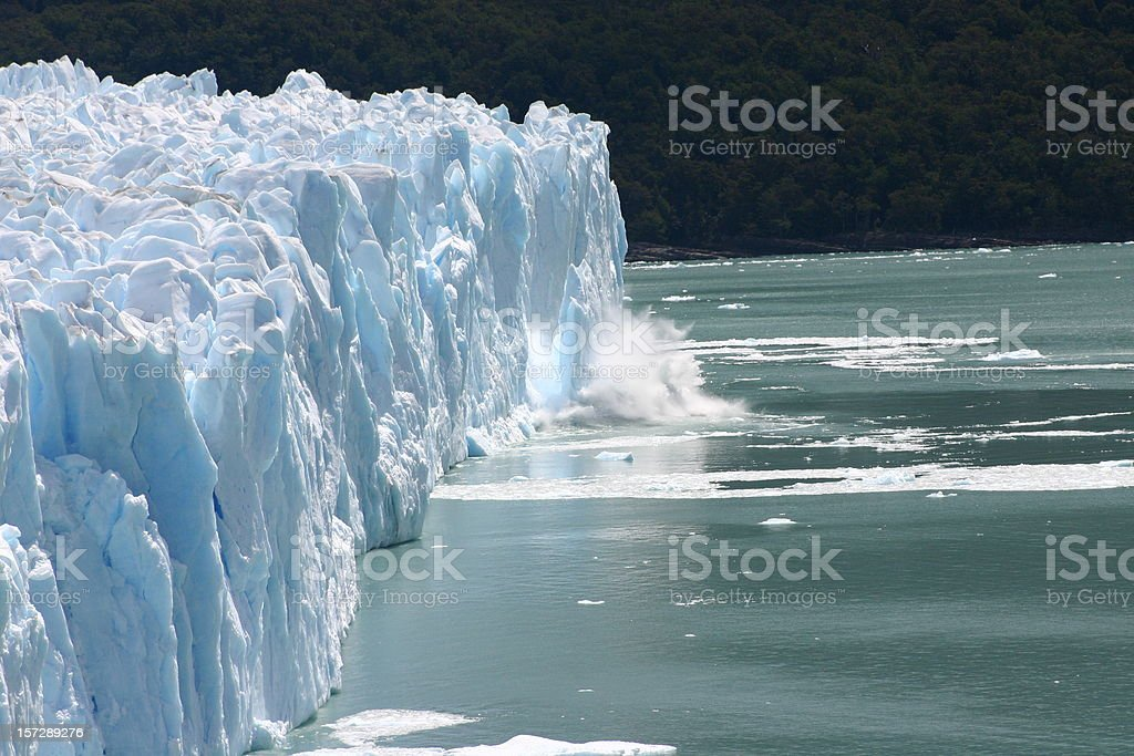 Ice falling from a glacier into the water stock photo