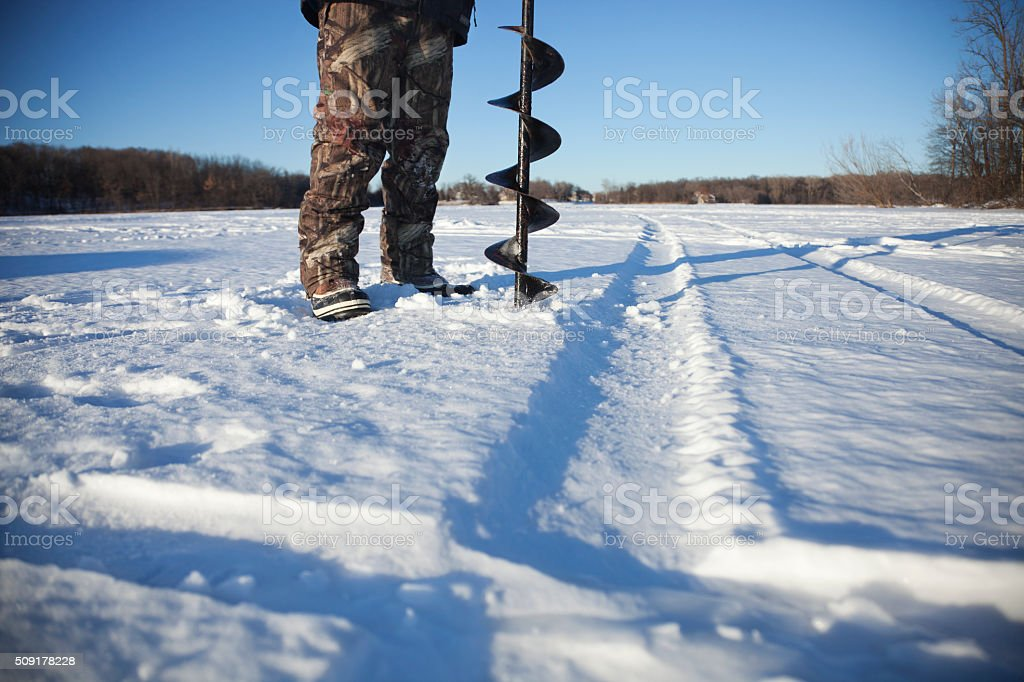 Ice fisherman drills hole with auger on lake in Minnesota stock photo