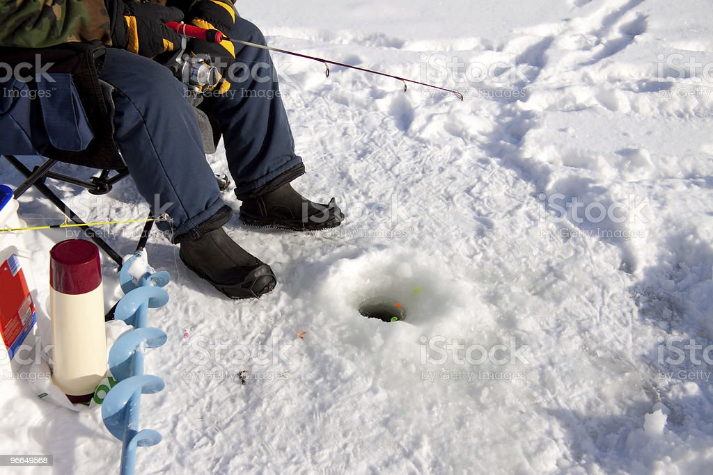 Ice fisherman waiting for a catch stock photo