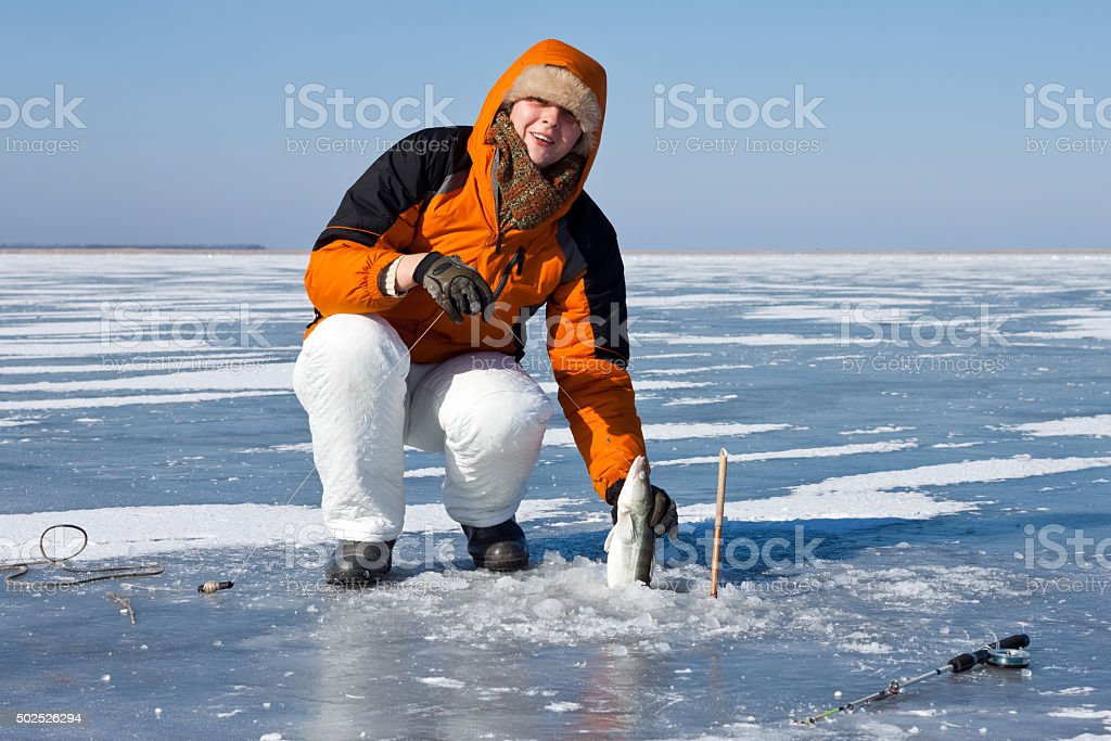 Ice fishing in the early morning. stock photo