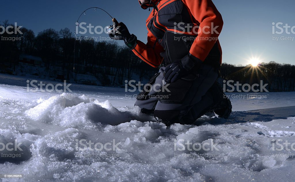 Ice fishing on a lake in winter stock photo