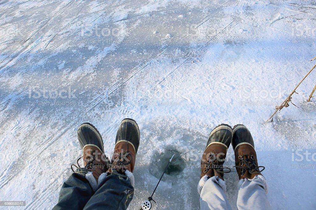 Ice fishing on frozen lake. stock photo