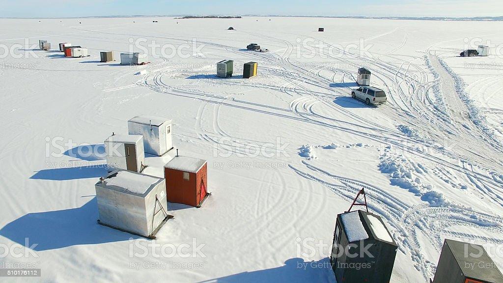 Ice fishing shanty village on frozen lake in winter stock photo