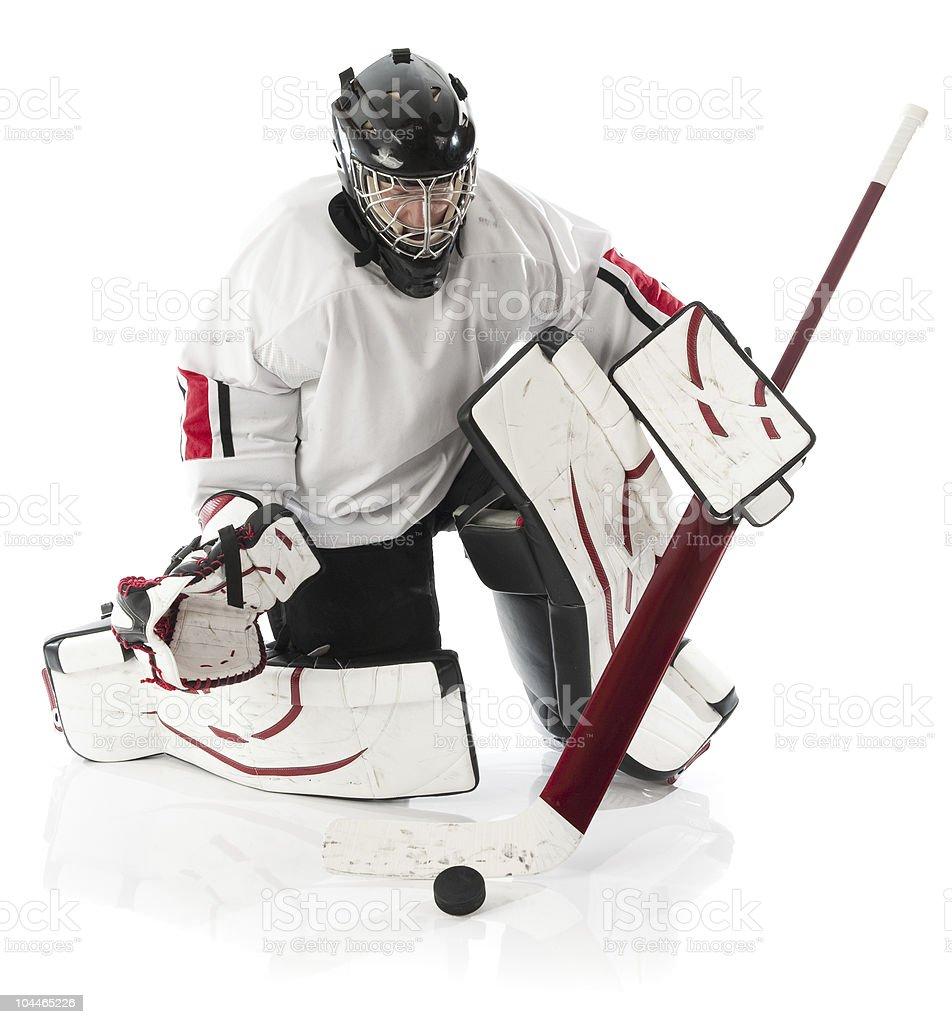 Ice hockey goalie kneeling on the field holding the stick stock photo