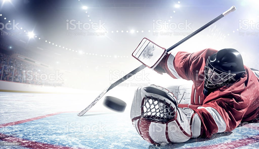 Ice hockey goalie trying to catch puck during game in indoor arena...