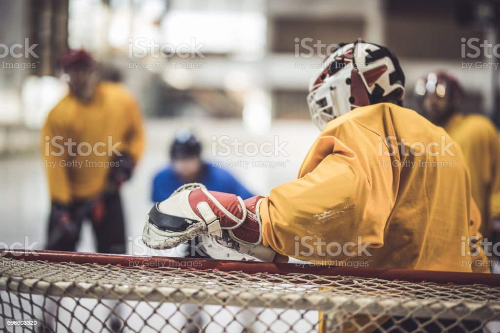 Ice hockey goalkeeper defending his goal on a match. stock photo