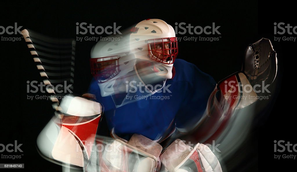 Ice hockey goaltender in action on a black background. stock photo