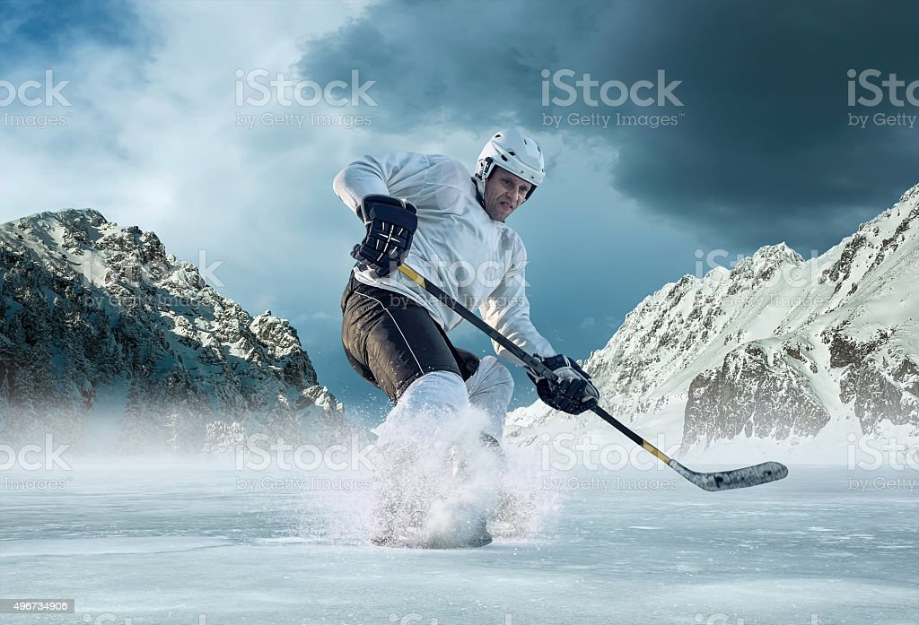 Ice hockey player in action outdoor around mountains stock photo