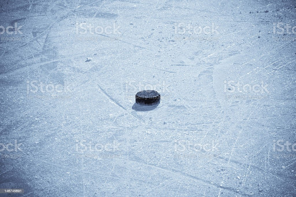 Ice Hockey puck isolated on ice stock photo