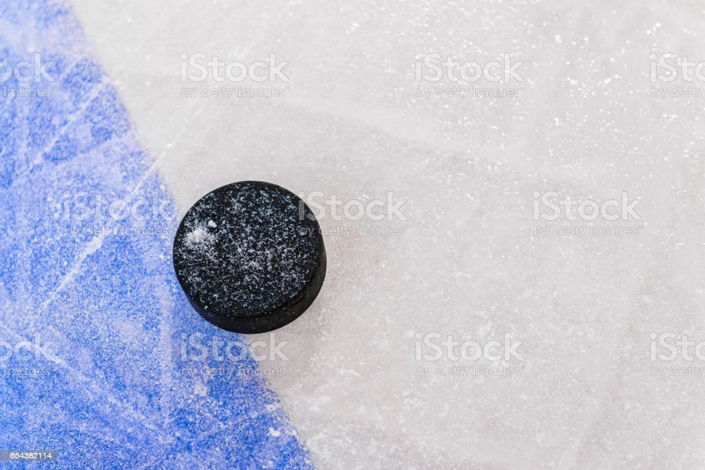 Ice Hockey puck next to Blue Line in rink stock photo