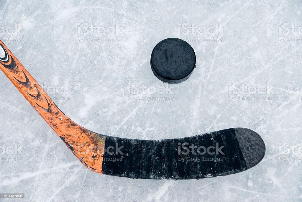 ice hockey stick and puck on ice stock photo