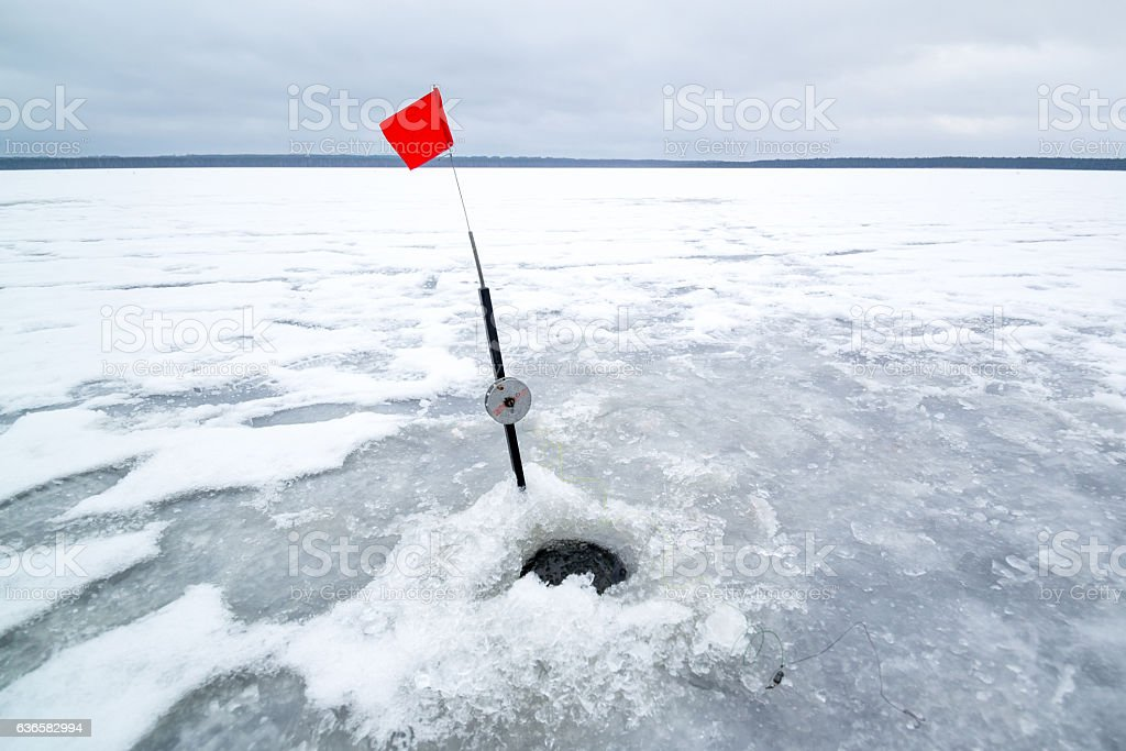 Ice hole in winter fishing and rod stock photo