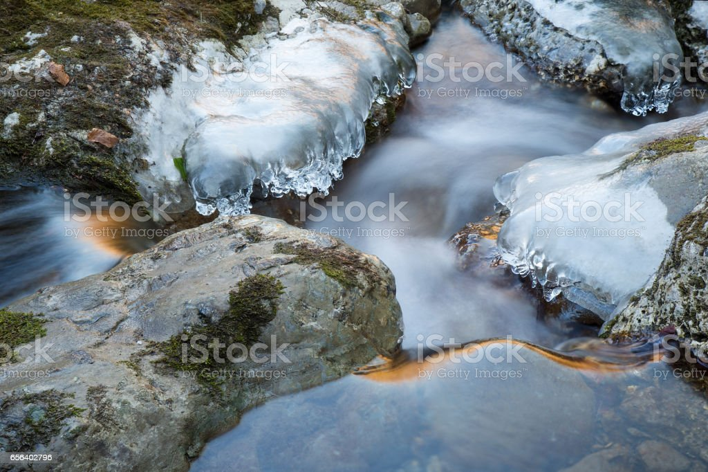 Ice on frozen rocks on River - Water motion with sun reflections stock photo