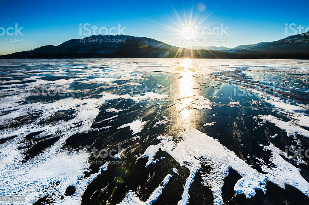 Ice on the frozen lake at sunset. stock photo
