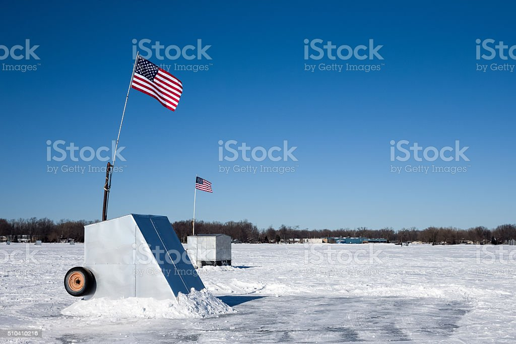 Ice Shanties on Frozen Lake with American Flags stock photo