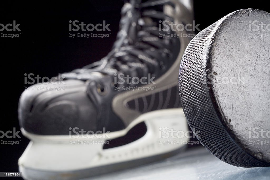 Ice skate and hockey puck royalty-free stock photo
