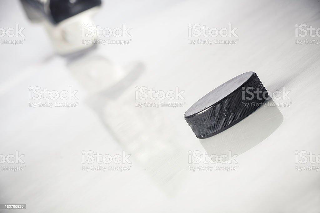 Ice skate and hockey puck royalty-free stock photo