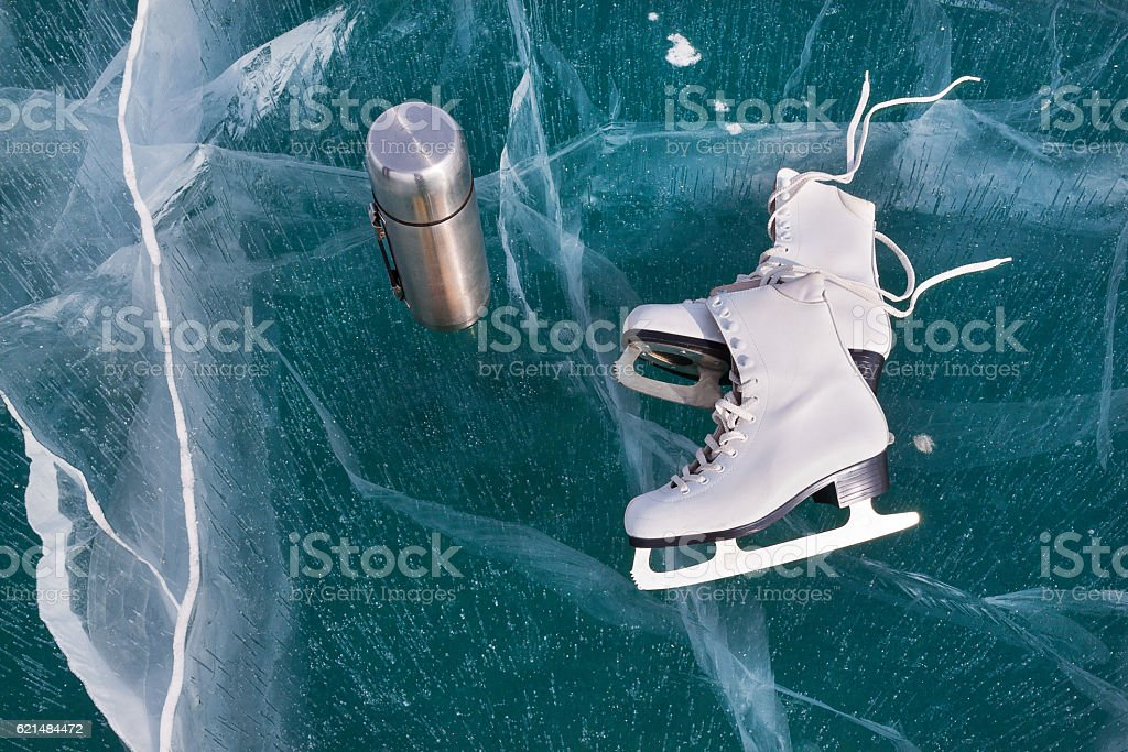 Ice skates at transparent cracked ice surface with thermos. Winter...