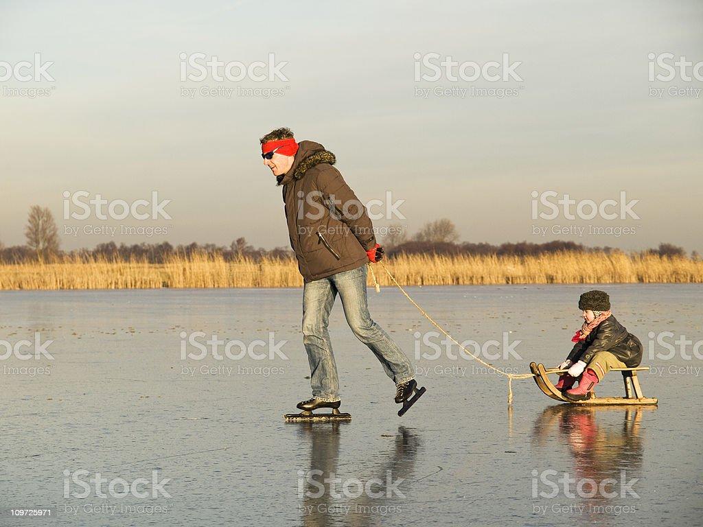 Ice Skating Man Pulling Child on Sled royalty-free stock photo