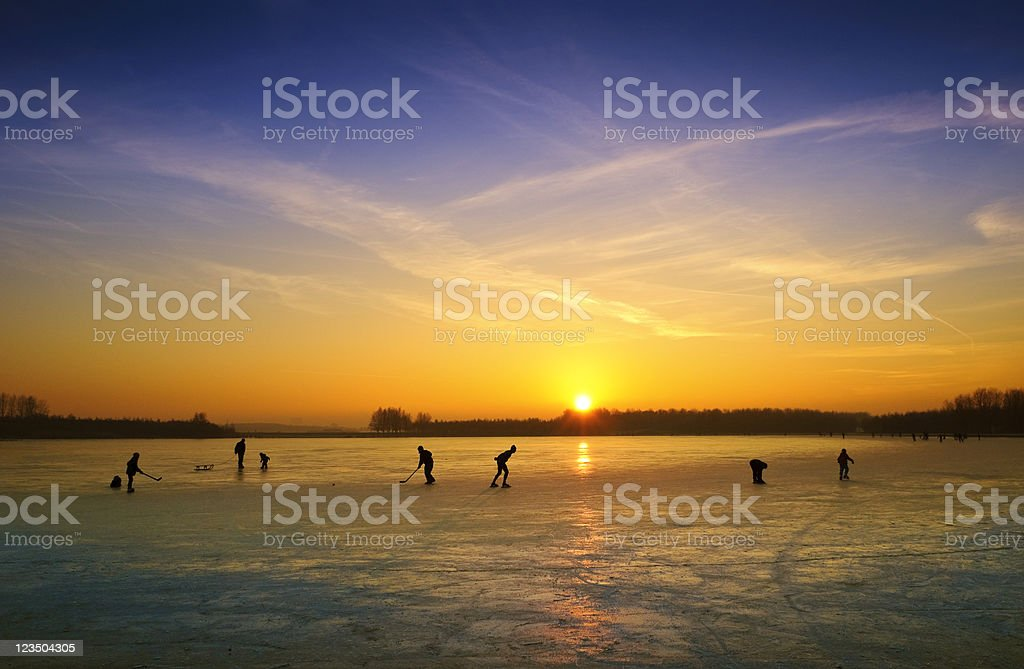 ice skating on a frozen lake at sunset royalty-free stock photo