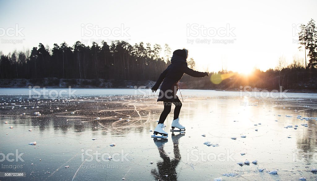 Ice skating on the frozen lake stock photo